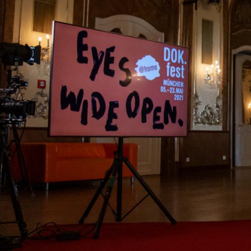 EYES WIDE OPEN: Im Studio des DOK.fest München 2021 @home kommen Filmschaffende aus der ganzen Welt nach München, dieses Jahr noch einmal digital. Dafür im glanzvollen Setting des Silbersaals des Deutschen Theaters