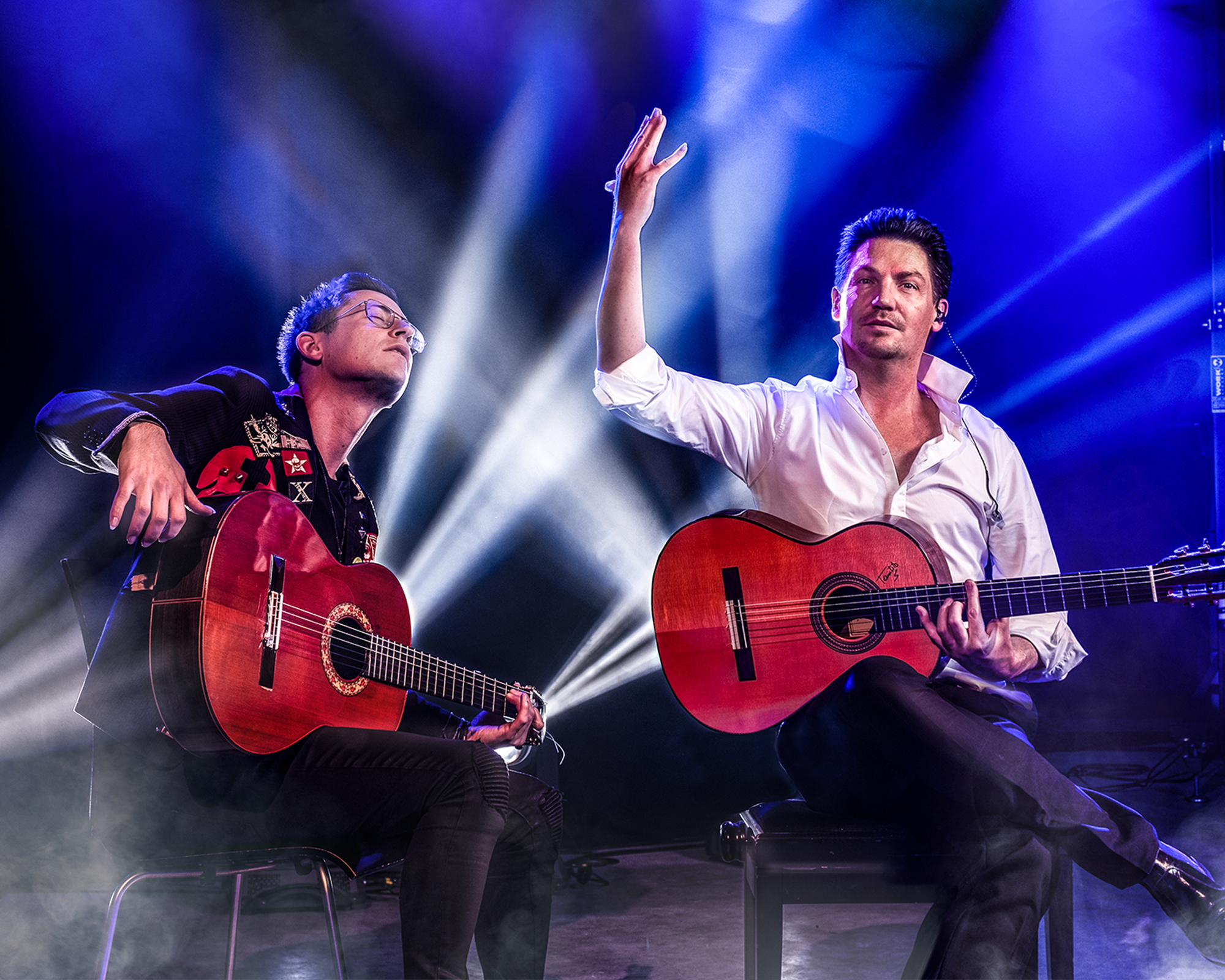 Zwei Männer mit Gitarre vor blauem Hintergrund