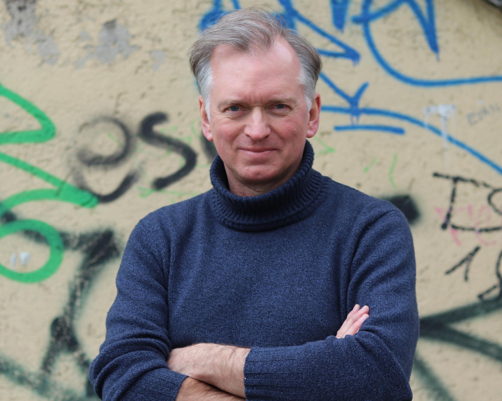 Christian Springer in blauem Rollkragenpullover vor einer Grafitiwand