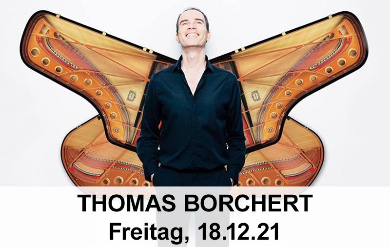 Thomas Borchert steht vor einem Piano, das hinter seinem Rücken aussieht, wie Flügel. Er lächelt und sein Blick geht nach oben.