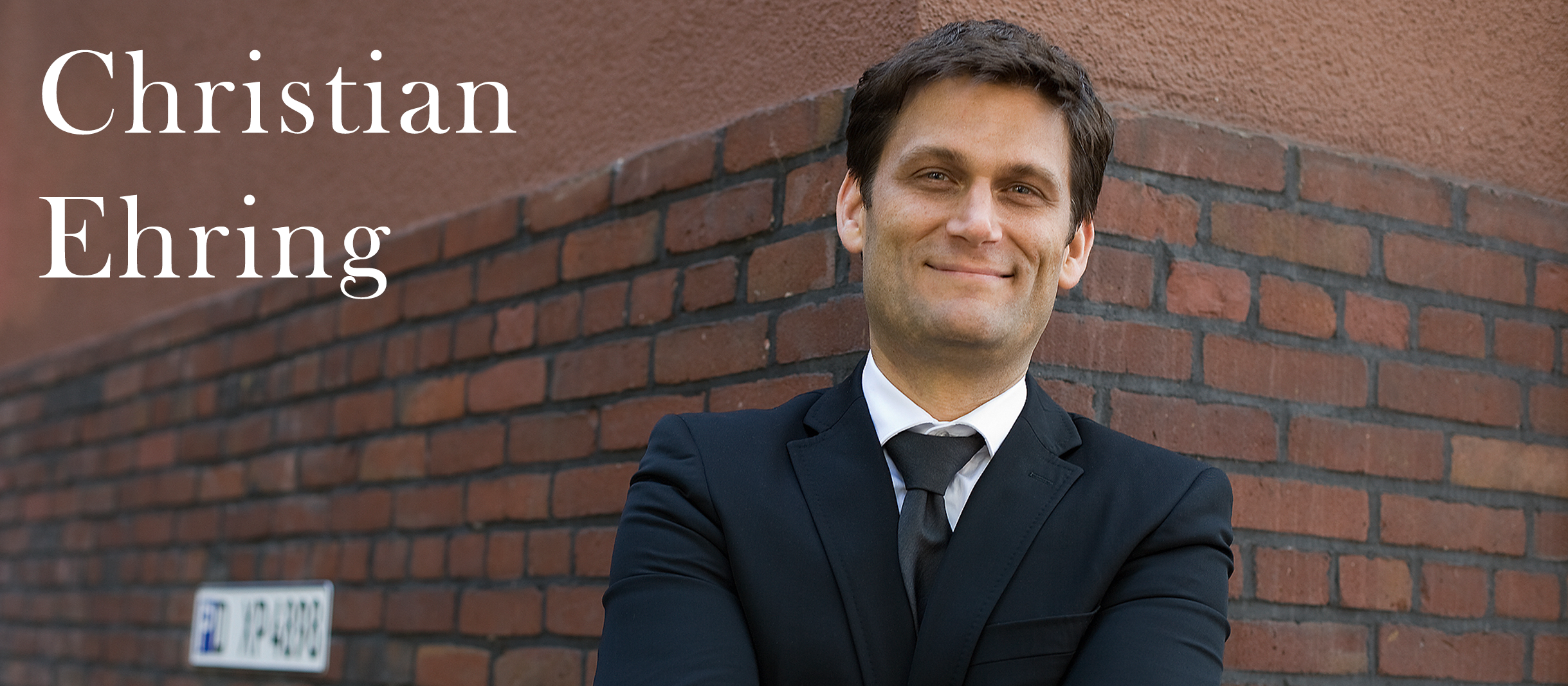 Christian Ehring lehnt lächelnd an einer roten Mauer