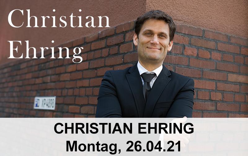 Christian Ehring lehnt an einer Steinmauer