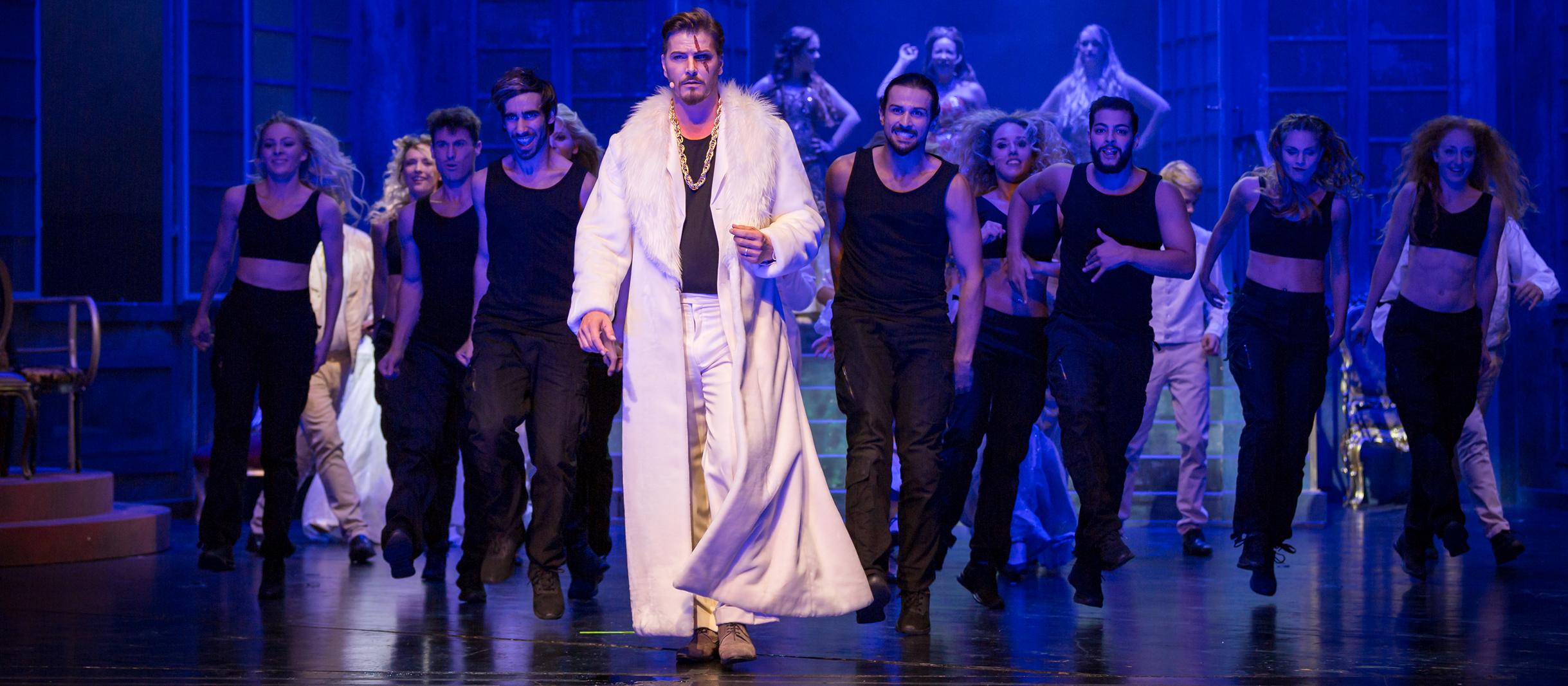 Ein Mann in weißem Mantel schreitet nach vorne. Hinter ihm laufen schwarz angezogene Menschen.