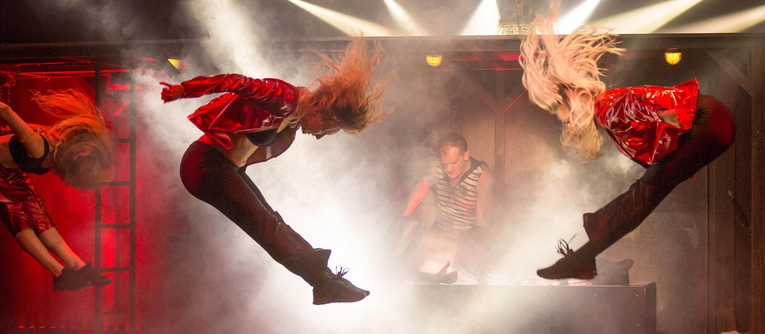 Zwei Tänzerinnen springen in die Luft. Im Hintergrund sieht man Alberich.