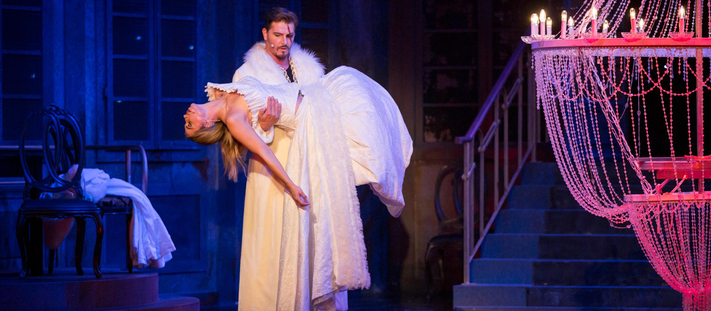 Ein Mann in einem weißen Mantel trägt eine Frau in weißem Kleid.