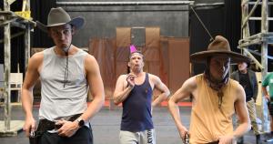Zwei grimmig schauende Cowboys und ein Indianer mit rosa Feder hinter einem dünnen Ast